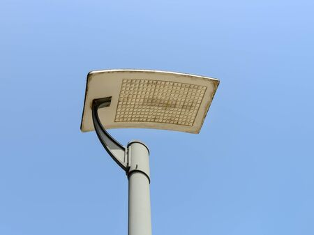 Led streetlight on a pole against clear blue sky background. Modern energy-saving technologies for lighting streets and roads. Led street lamp. Low angle view.