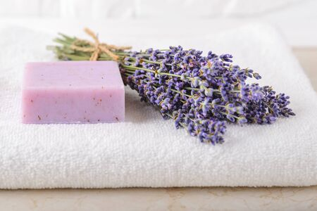 Fresh fragrant lavender and purple lavender soap on a white terry towel in a bathroom. Home made spa, skincare and cosmetology concept. Front view. Reklamní fotografie