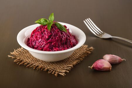 Grated boiled beet salad with garlic and mayonnaise in a white bowl on a brown table. Side dish and vegetarian garnish. Russian cuisine. Front view.