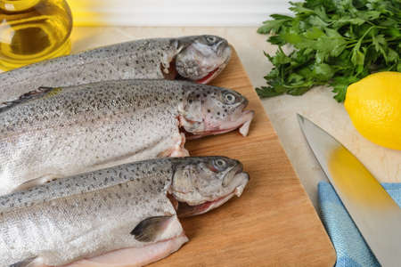 Close-up of three raw gutted trout fishes on a wood cutting board prepared for cooking. Fresh fish dishes, healthy eating and cook at home concept. Top view.