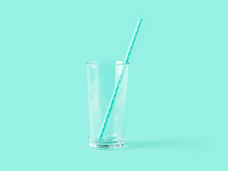 Empty tall transparent glass and paper drinking straw on mint green color background. Modern stylish tableware. Copy space. Front view.