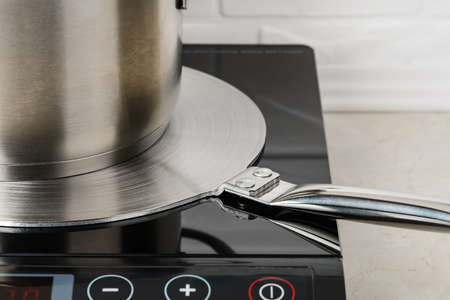 Cookware on a stainless steel heat diffuser plate over a cooktop. Kitchen appliance for induction hob allows to use small diameter or non-ferromagnetic cookware. Close-up.