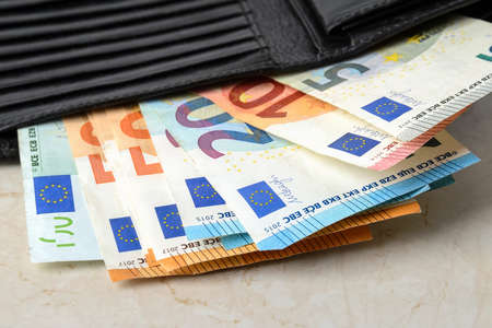 Euro banknotes of different face value in a black leather wallet close-up. Wealth, cash savings, accounting of income and expenses concept. Front view. Фото со стока