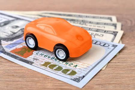 Orange toy car on few 100 dollar banknotes. Concept of car buying, renting, service, repair and insurance costs. Save money for an expensive purchase. Planning for expenses. Front view.