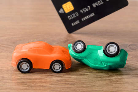 Orange and green toy car crush accident and credit card. Concept of car buying, renting, service, repair and insurance costs. Planning for expenses. Front view.