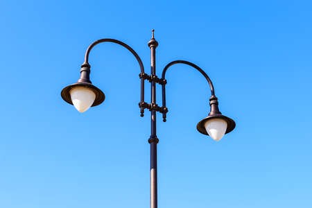 Street lamp with two bulbs against a blue sky on a sunny day. Vintage style double lamp post outdoors. Modern energy-saving technologies for lighting streets, parks and roads. Low angle view.