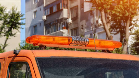 Orange warning lightbar on a stationary car tow track parked on a city street on a summer sunny day. Roof mounted lightbar on a automotive technical assistance vehicle. Close-up. Stock fotó
