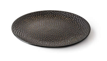 Side view of round black ceramic plate with textured surface isolated on a white background. Empty crockery for food design. Modern clay, ceramics or porcelain dishes and tableware. Close-up.