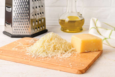 Wedge of italian hard cheese Grana Padano or Parmesan and heap of grated cheese on a wood cutting board near stainless steel kitchen grater over white wood table. Front view. Archivio Fotografico