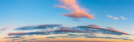 Vanilla sunset sky panoramic shot. Pink golden blue evening sky with long stratus clouds over the horizon. Pastel colored calm skyscape. Beauty in nature.