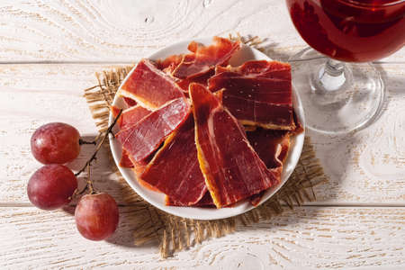 Sliced jamon on a plate, few pink grapes and wine glass over white wood table. Hard light shot. Traditional spanish jamon Serrano. Tasty meat delicacy. Close-up. Top view.