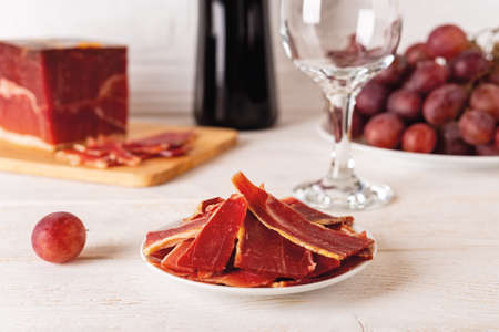 Sliced jamon on a plate against large jamon piece on a cutting board, bunch of pink grapes, wine bottle and glass over white wood table. Tasty spanish jamon Serrano. Front view.