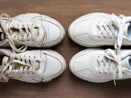 Pair of old dirty white sneakers in front of new clean one on a brown background. Past and future, old and new concepts. Comfortable shoes for active lifestyle, fitness and sports. Top view.