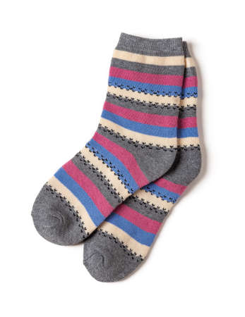 Pair of tall striped socks isolated on a white background. Gray socks with white, blue, pink stripes. warm clothing and hosiery for the cold winter season. Top view.