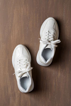 Pair of white tied laces sneakers on a brown background. New unisex chunky sole shoes for active lifestyle, fitness and sports. Copy space. Top view. 免版税图像 - 158363912