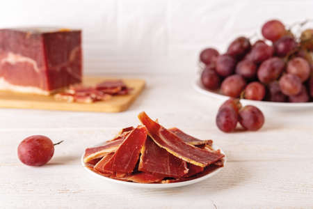 Sliced jamon on a plate against large jamon piece on a cutting board and bunch of pink grapes over white wood table. Traditional spanish jamon Serrano. Front view.