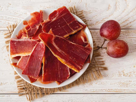 Sliced jamon on a plate and two large pink grapes over white wood table. Traditional spanish jamon Serrano. Tasty meat delicacy. Top view.