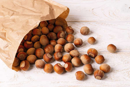 Unpeeled hazelnuts spilled out of a paper bag onto the white wood table. Nuts as an antioxidant and protein source for ketogenic diet and vegetarianism. Top view. 免版税图像