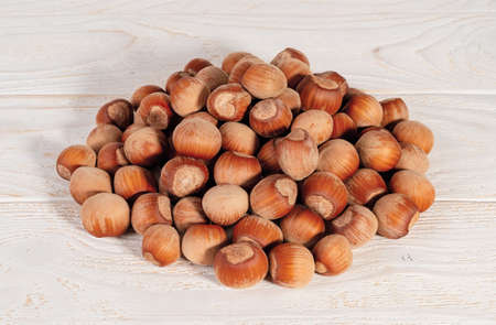 Pile of unpeeled hazelnuts over white wood table. Nuts as an antioxidant and protein source for ketogenic diet and vegetarianism. Top view.