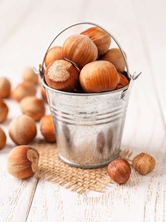 Hazelnuts in a small metal bucket over white wood table. Healthy vegetarian eating, antioxidant and protein source. Ketogenic and raw food diets. Harvest concept. Front view.