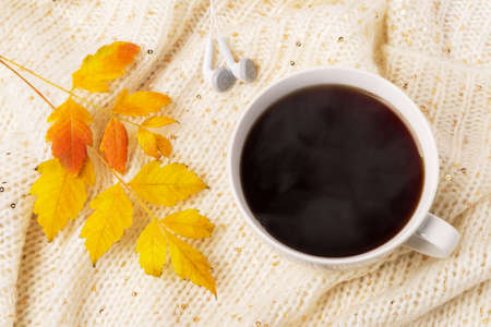 Large white mug of hot steaming coffee, earphones and yellow fall leaf on a beige knitted scarf. Cozy autumn mood concept. Top view. 免版税图像