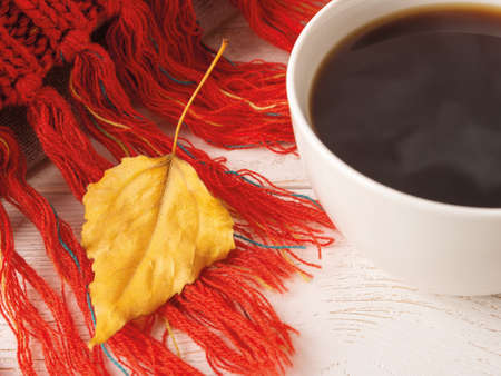 Close-up of dry yellow fall leaf on a knitted red fringed scarf near white mug of hot steaming coffee. Cozy autumn mood concept. Selective focus. Top view.
