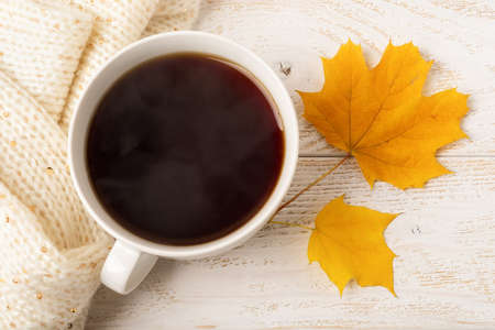 Large white mug of hot steaming coffee and two yellow fall leaves near beige knitted scarf over white wood rustic surface. Cozy autumn concept. Top view. 免版税图像