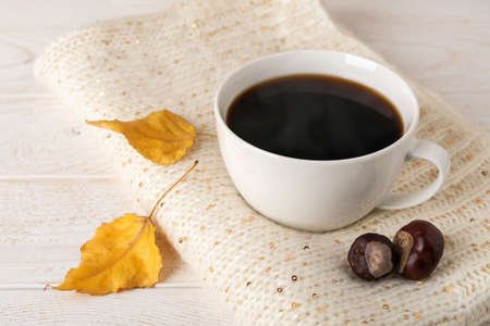 Large white mug of hot steaming coffee on a beige knitted scarf and two yellow fall leaves over white wood rustic surface. Cozy autumn mood concept. Front view. 免版税图像
