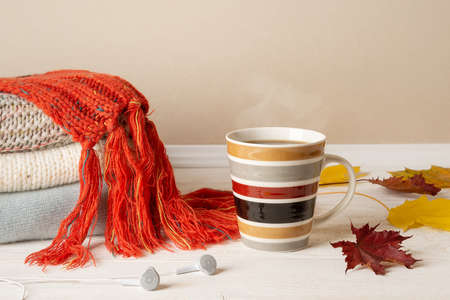 Striped mug of hot steaming coffee or tea, stack of warm knitted sweaters and red fringed scarf and few yellow fall leaves over white wood rustic surface. Cozy autumn mood concept. Front view.