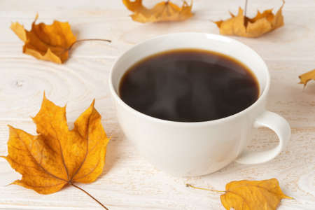 Large white mug of hot steaming coffee and few dry yellow fall leaves over white wood rustic surface. Cozy autumn mood concept. Front view.