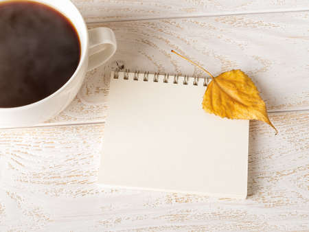 Bright yellow autumn leaf on the open spring notepad near large mug of hot steaming coffee over white wood table. Empty page for copy space. Top view.