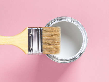 Close-up of new natural bristle brush with wooden handle on an open white paint can over pastel pink textured background. Construction painting work, repair and redecorate concepts. Top view. 免版税图像