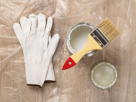 New natural bristle brush with wooden handle on an open white paint can near lid and white textile gloves over cellophane covered floor. Construction painting work, repair and redecorate concepts. Top view.