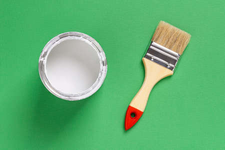 New natural bristle brush with wooden handle near open white paint can on a grassy green textured background. Construction painting work, repair and redecorate concepts. Top view.