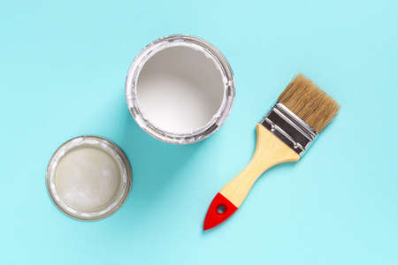 New natural bristle brush with wooden handle, open white paint can and lid on a cyan blue background. Construction painting work, repair and redecorate concepts. Top view. 免版税图像