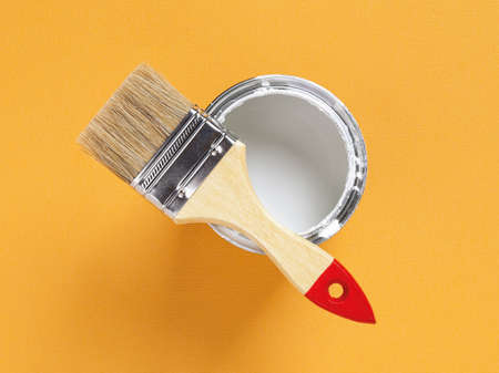 New natural bristle brush with wooden handle on the edge of an open white paint can over bright yellow textured background. Construction painting work, repair and redecorate concept. Top view.