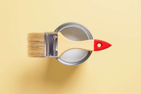 New natural bristle brush with wooden handle on an open white paint can over pastel yellow background. Construction painting work, repair and redecorate concepts. Top view.
