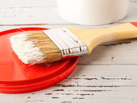 New natural bristle brush with white paint on a red plastic lid over scratched paint wood surface. Construction painting work, repair and redecorate concepts. Close-up.