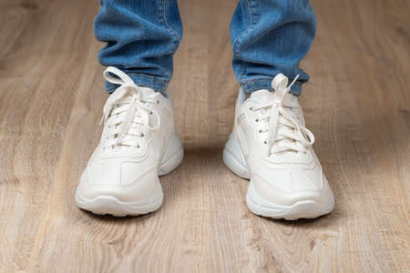 Standing feet shod in white lace-up chunky sole sneakers and blue jeans on the brown floor. Pair of new comfortable shoes for active lifestyle, everyday life and sports. Low angle view.