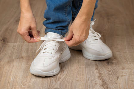 Caucasian woman hands tie elastic laces on chunky sole white sneakers shod on her feet on the brown floor. Pair of new comfortable shoes for active lifestyle, everyday life and sports. Low angle view.