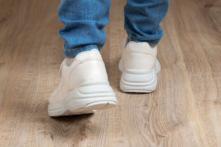 Rear view of walking feet shod in white chunky sole sneakers and blue jeans on the brown floor. Pair of new comfortable shoes for active lifestyle, everyday life and sports. Low angle view.