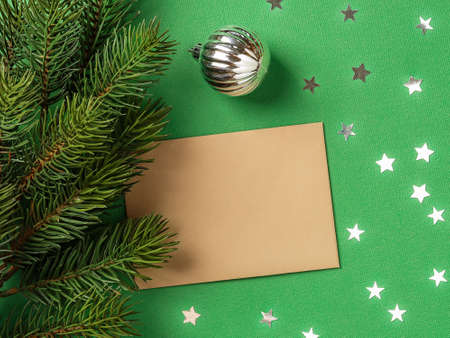 Blank brown greeting card and silver christmas ball near spruce branch on a textured green background with silver stars. Winter season holidays Christmas and New Year. Copy space. Top view.
