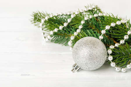 Silver glitter christmas ball near spruce branch decorated with a silver bead garland on a white wood table. Greeting card for Christmas and New Year. Shallow DoF. Copy space. Front view. 免版税图像
