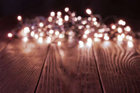 Blured shining christmas lights garland on a dark wood tabletop. Glowing LED lightning decorations in a darkness. Winter season holidays Christmas and New Year. Copy space. Front view.