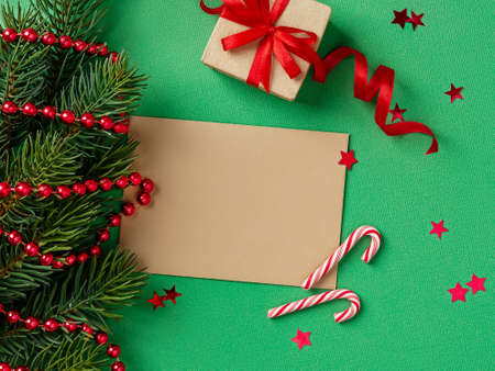 Blank brown greeting card and small gift box with red ribbon near spruce branch on a textured green background. Winter season holidays Christmas and New Year. Copy space. Top view. 免版税图像