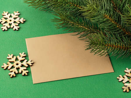 Blank brown greeting card, few wooden snowflakes and spruce branch on a textured green background. Winter season holidays Christmas and New Year. Copy space. Top view.