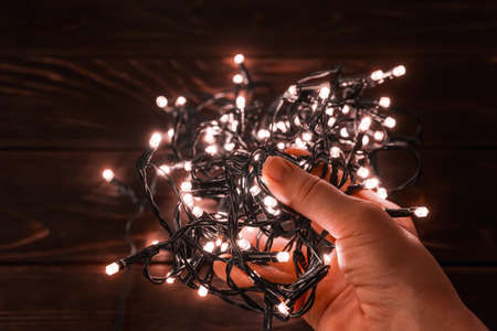 Woman hand holds shining christmas lights garland in a darkness. Glowing LED lightning in a palm. Decorations for winter season holidays Christmas and New Year. Top view. 免版税图像