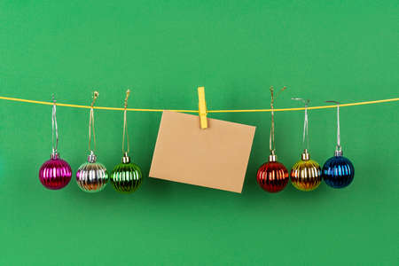 Multicolored christmas balls and Blank brown greeting card on a hanging on a string against green background. Winter season holidays Christmas and New Year. Copy space. Front view. 免版税图像