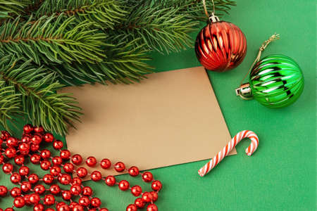 Blank brown greeting card, two christmas balls, red bead garland and spruce branch on a textured green background. Winter season holidays Christmas and New Year. Copy space. Top view. 免版税图像
