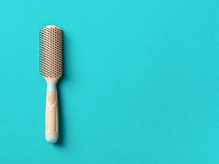 New beige hair brush with handle on a textured marine blue background. Combing and hair care, hairdressing tools, haberdashery. Studio shot. Copy space. Top view. 免版税图像